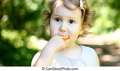 A child on the nature in the park sits and eats an orange candy. Lollipop