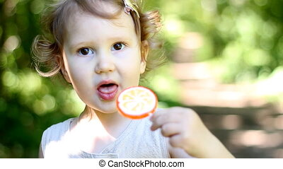 A child on the nature in the park sits and eats an orange candy.