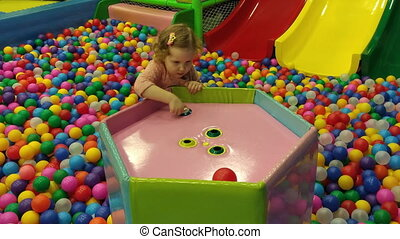 A child on the playground plays with colored balls. Children's games and entertainment for children.