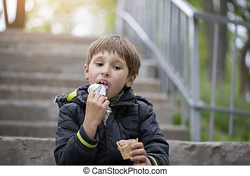 A child on the street eats ice cream. Boy with a sweet dessert in the park.