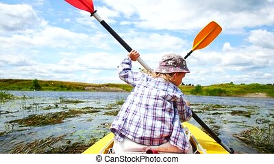 A child paddles on a kayak paddle. Active family vacation. -...