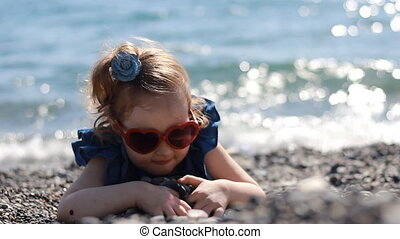A child play by the sea on a pebble beach on a windy sunny day with glasses in the form of a heart.