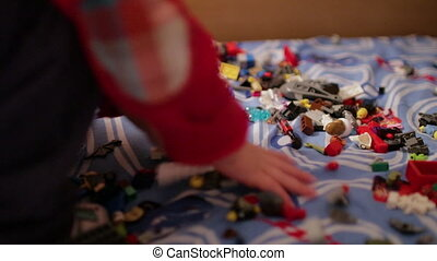 A child playing in the children's designer on the bed