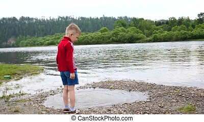 A child playing on the banks of the river, the Beautiful summer landscape. Outdoor recreation.