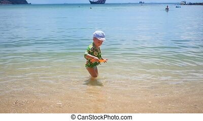 a child playing on the beach sand in Sunny day