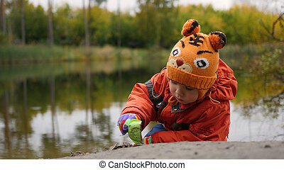 A child playing on the shore of the pond. Walks in the fresh air. Autumn landscape. The reflection of sky and trees in the water of the lake. A beautiful scenic place