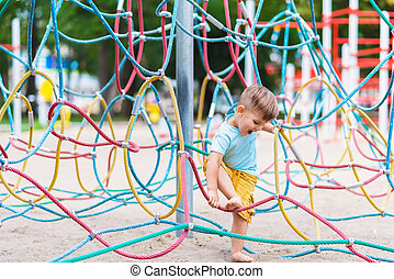a child plays in a rope web on the playground in the park