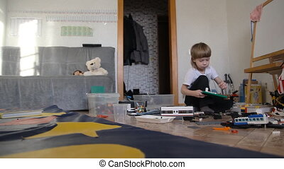 A child plays in the constructor and toys. Boy sitting on...