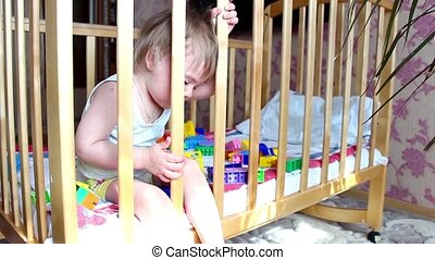 a child plays in the crib
