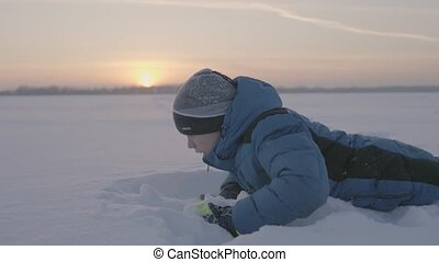 A child plays in the snow at sunset. Fun and games in the fresh air