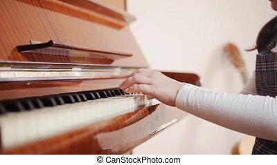 A child plays piano and close up a piano cover. Close up