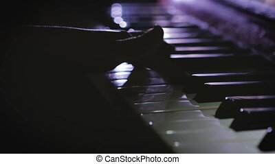 A child plays the piano - Close-up of baby girl's hands...
