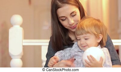 a child plays with a ball with mom