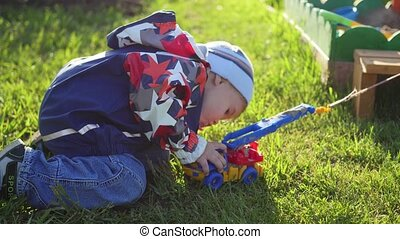 a child plays with a toy car on the lawn. Fun and games outdoors