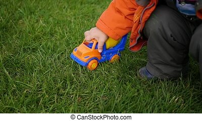 a child plays with a toy car on the lawn