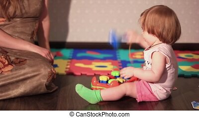 a child plays with a toy on the floor