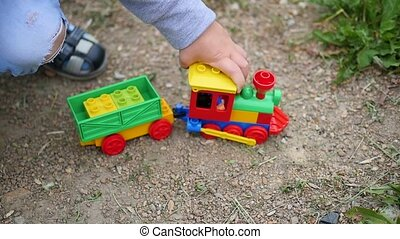 A child plays with a toy train on the sand. Outdoor games