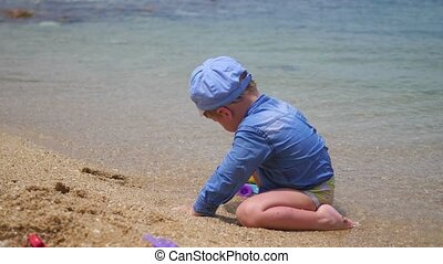 A child plays with sand and toys on the beach on a sunny hot day
