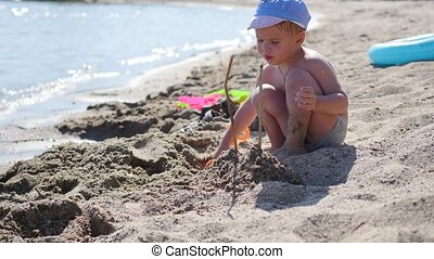 A child plays with sand and toys on the beach on a sunny hot day. Entertainment and outdoor games