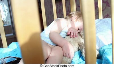 a child plays with teddy bear in the crib