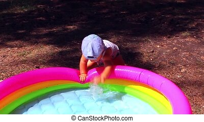 a child plays with water in the pool