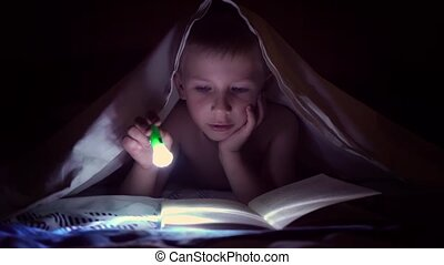 A child reads a book under blankets with a flashlight at...