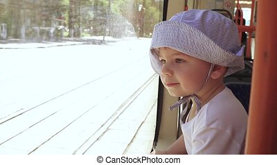 A child in a panama ride on a tram and look out the window