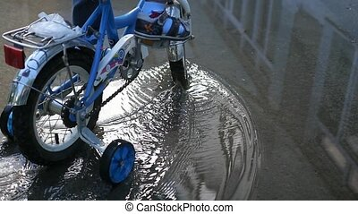 A child riding a children's bike through the puddles