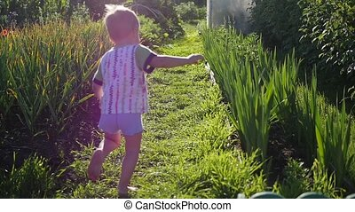 A child runs barefoot across the lawn. Fun outdoors