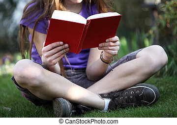 A child sits in the garden and read a book