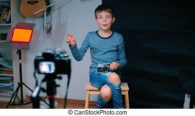 A child sits on a chair in front of a video camera.