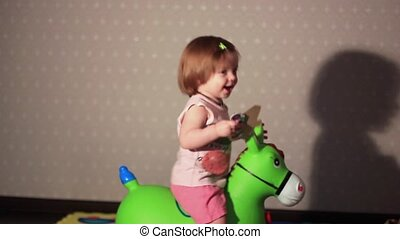a child sits on a toy horse