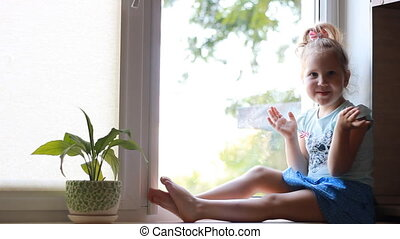 A child sits on a window sill and looks out the window.