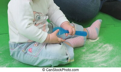 A child sits on floor and plays with a spoon