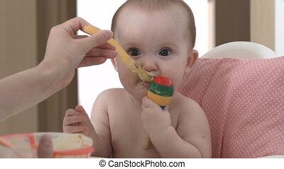 A child smiles and eats porridge