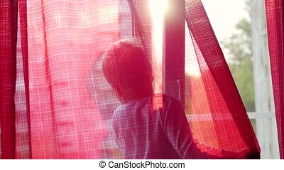 a child stands on the windowsill and looking out the window at the sun. on the window red curtains