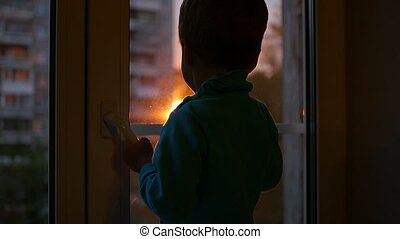 a child stands on the windowsill and looking out the window at the sun. Sunset
