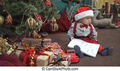 A child with a letter to santa chews pen and smiling