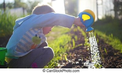 A child with a small watering can water the grass in the yard. Young gardener