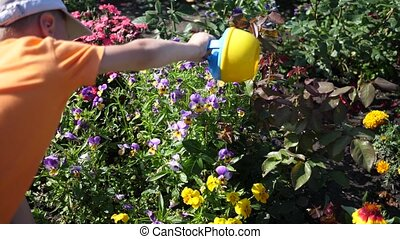 A child with a small watering can watering flower garden....