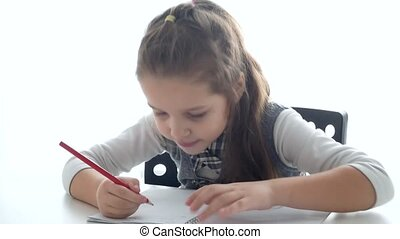 A child with a tablet and a book. A schoolgirl learns with a...