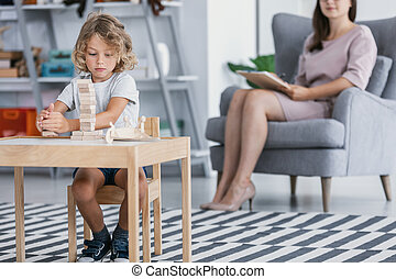 A child with Asperger Syndrome playing with wooden blocks during a therapeutic meeting with a therapist in a family support center.