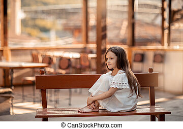 A child with bare feet sits on a wooden bench.