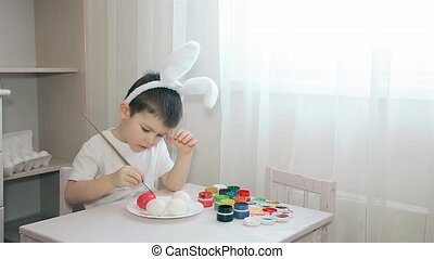 A child with Bunny ears on his head paints an Easter egg in pink