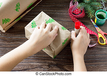 A child wraps paper with Christmas gifts box and a snowman of sweets. Made by own hands. Children's art project for children. Craft for kids.