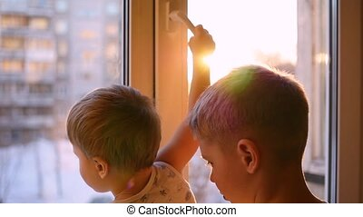 a children looks out the window through the sun in slowmotion