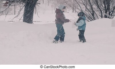 A children playing in the park in the snow. Portraits of two boys.