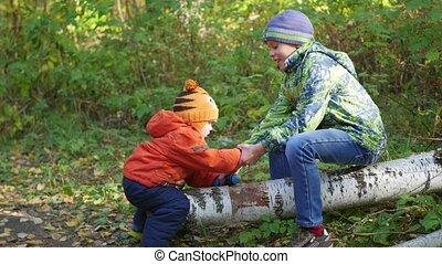 a children swinging on a fallen tree in the Park