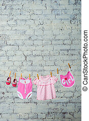 A children's pink bodik, a bib, a dress and red shoes for a girl, dry on a rope against a white brick wall.