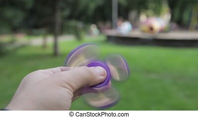 A children's toy is a spinner in the hand of an adult.